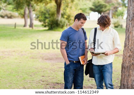 Two standing male students talking in a park - stock photo