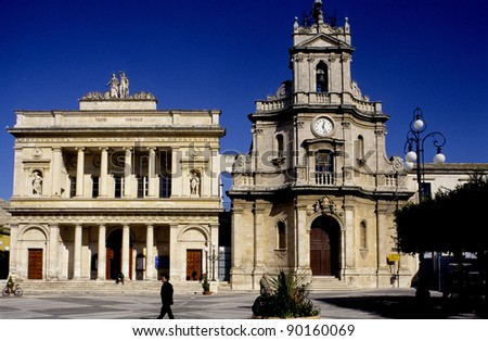 two statues atop a historical building, public theater colonna, ragusa, sicily, italy, europe - stock photo