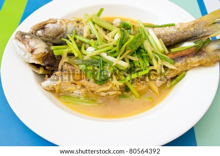 two steamed mackerel fishes with ginger on white plate