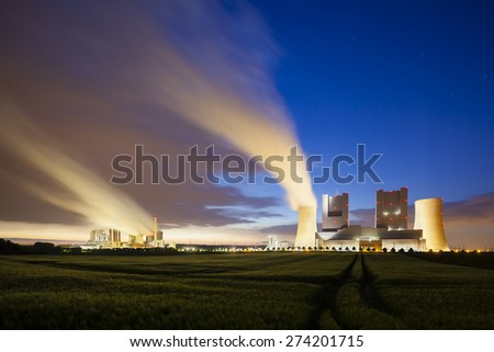 Two steaming coal-fired power stations behind a field at night - stock photo