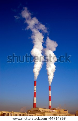 Two steaming pipes of power plant against blue sky - stock photo