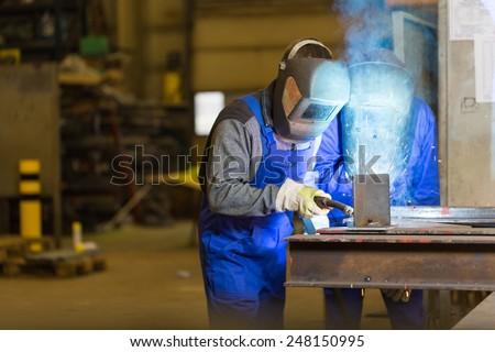 Two steel construction workers welding metal in workshop - stock photo