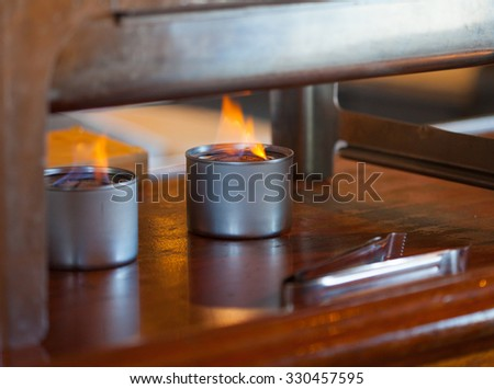 Two sternos with flames under a warming buffet tray - stock photo