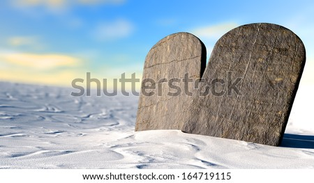 Two stone tablets representing the ten commandments standing in brown desert sand in front of a blue sky - stock photo