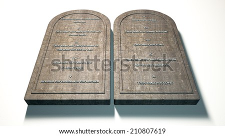 Two stone tablets with the ten commandments inscribed on them standing in brown desert sand in front of a blue sky - stock photo