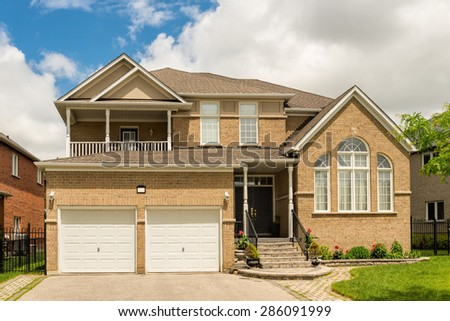 Two storey house with a lawn and driveway - stock photo