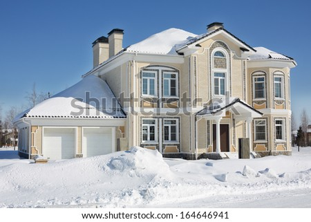 Two-storey light cottage with garage at frosty and sunny winter day. - stock photo