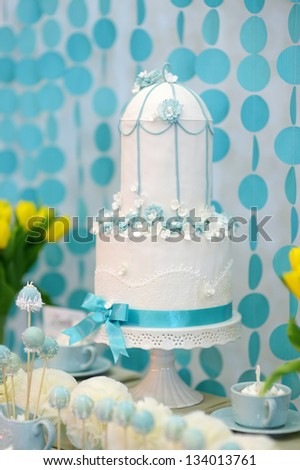 Two stories wedding cake decorated with blue flowers - stock photo