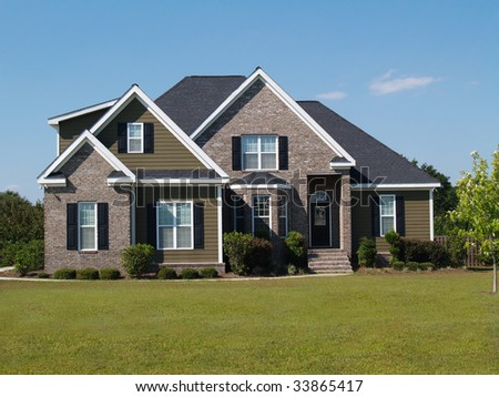Two story brick and vinyl residential home.