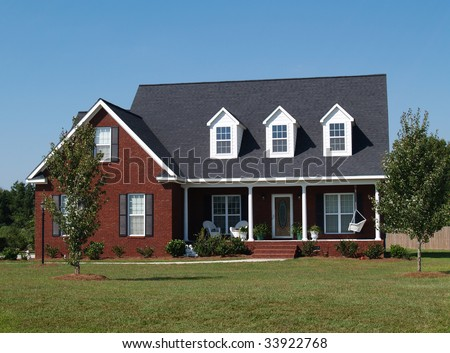 Two story brick residential home with porch swing. - stock photo