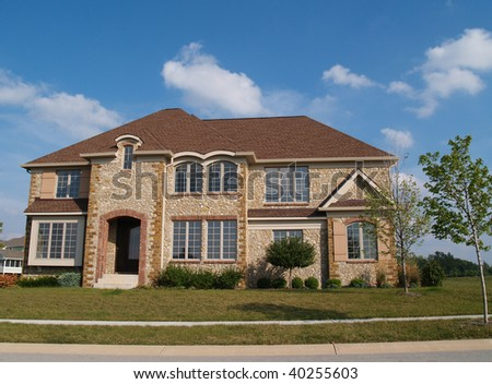 Two story contemporary stone residential home with arched windows.