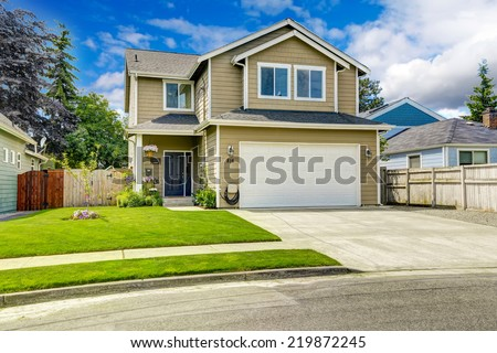 Two story house exterior with white door garage and driveway - stock photo