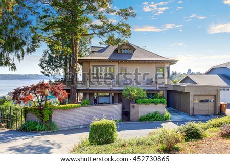 Two story house with beige brick, tile roof and beautiful curb appeal. - stock photo