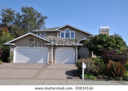 Two story house with driveway and mailbox - stock photo
