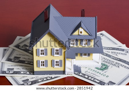 Two-story house with five dollar bills background - stock photo
