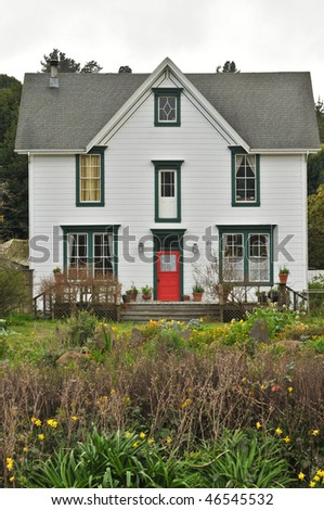 Two story house with red door and landscape