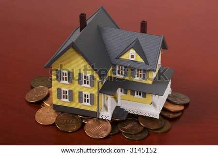 Two-story house with red wooden background and pennies - stock photo
