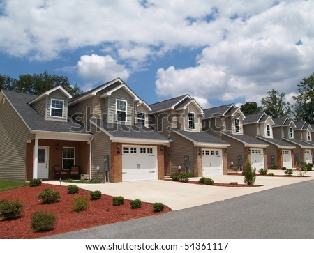 Two story low income retirement homes with the garage in the front. - stock photo