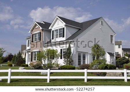 Two story modern home with a white wooden fence around the yard - stock photo