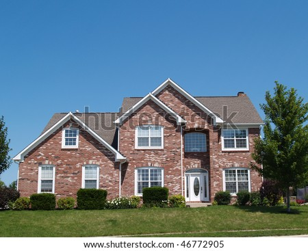 Two story new brick residential home with side garage and plenty of copy space. - stock photo
