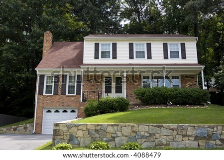 Two story red brick house with shutters on windows