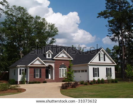 Two story residential home with brick and board siding on the facade. - stock photo
