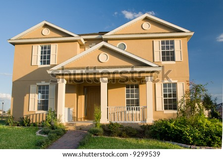 two-story stucco home with landscaped lawn - stock photo