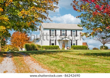 Two story white wood siding farm house in the countryside in autumn.