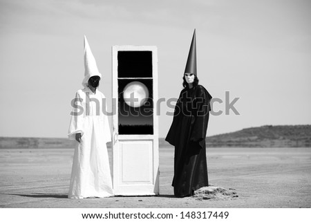 Two strange people in black cloak and white cloak and the door to the moon. Artwork