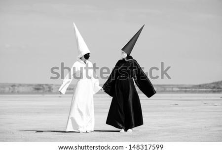 Two strange people in black cloak and white cloak talking. Artwork - stock photo