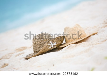 Two straw hats on white sand tropical beach - stock photo