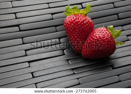 Two strawberries on a black tile background - stock photo