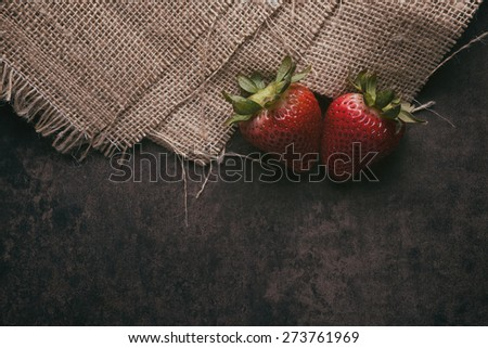 Two strawberries on a rustic background - stock photo