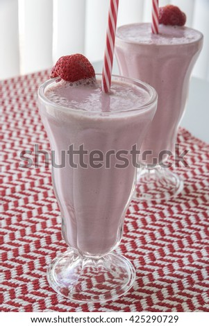 Two strawberry shakes on a red and white herringbone pattern table cover in front of a window