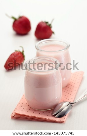Two strawberry yoghurt jars  with fresh strawberries on white background