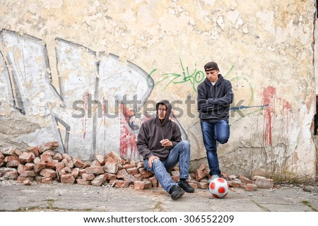two street hooligans or rappers standing against a graffiti painted wall are preparing to smoke a cigarette - stock photo