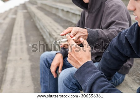 two street hooligans or rappers standing outdoor share a cigarette - stock photo