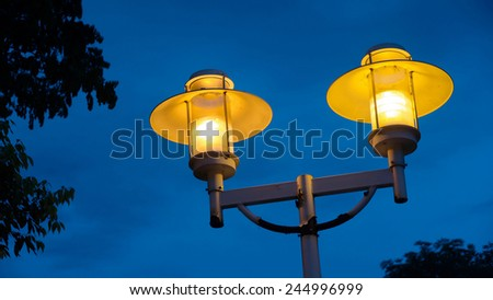 Two Street Lamps of Warm Yellow Color on A Pole, Against Cold Background of Blue Sky And Tree Leaves in Dark Color. - stock photo