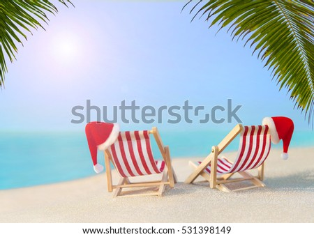 Two striped red-white sunloungers with Christmas Santa hats for romantic couple at ocean sandy sunset beach under big palm leaves, New Year travel destinations concept for vacation in hot countries