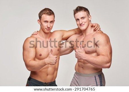 Two strong athletic men shirtless gesturing thumbs up