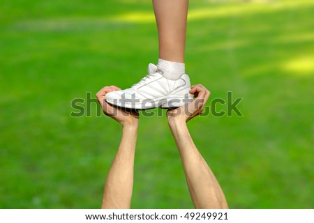 Two strong male hands holding one female foot. Teamwork, support, competition concept - stock photo