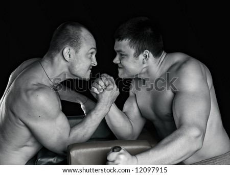 Two strong mans armwrestling in atheletic common-room - stock photo