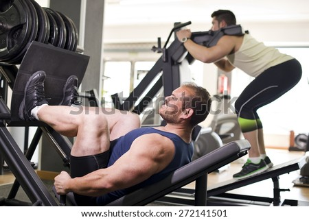 Two strong men at gym traning legs with press.
