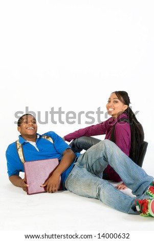 Two Students are sitting on the ground smiling at the camera. Both wear backpacks and he carries a notebook. Vertically framed photograph - stock photo
