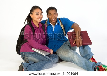 Two Students are sitting on the ground smiling at the camera. Both wear backpacks and he carries a notebook. Horizontally framed photograph - stock photo