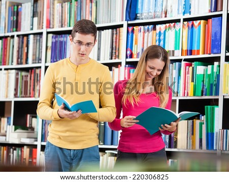 Two students browse through the books in the library.