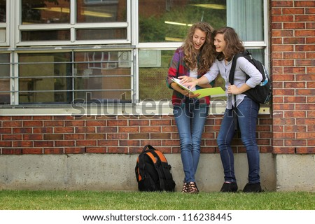 Two students girls looking at their lessons after school
