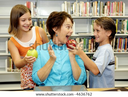 Two students giving apples to their favorite teacher.  She is very surprised and happy. - stock photo