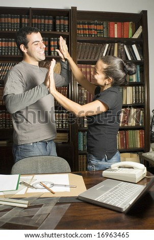 Two students giving each other high fives in a library. Vertically framed photo. - stock photo