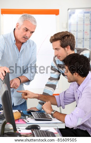 Two students having discussion with teacher - stock photo